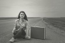 Girl Siting On Road With Suitcase Looks For Fellow Traveler Stock Images
