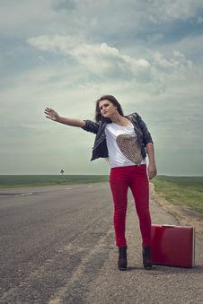 Girl Standing On Road With Suitcase Looks For Fellow Traveler Royalty Free Stock Photography