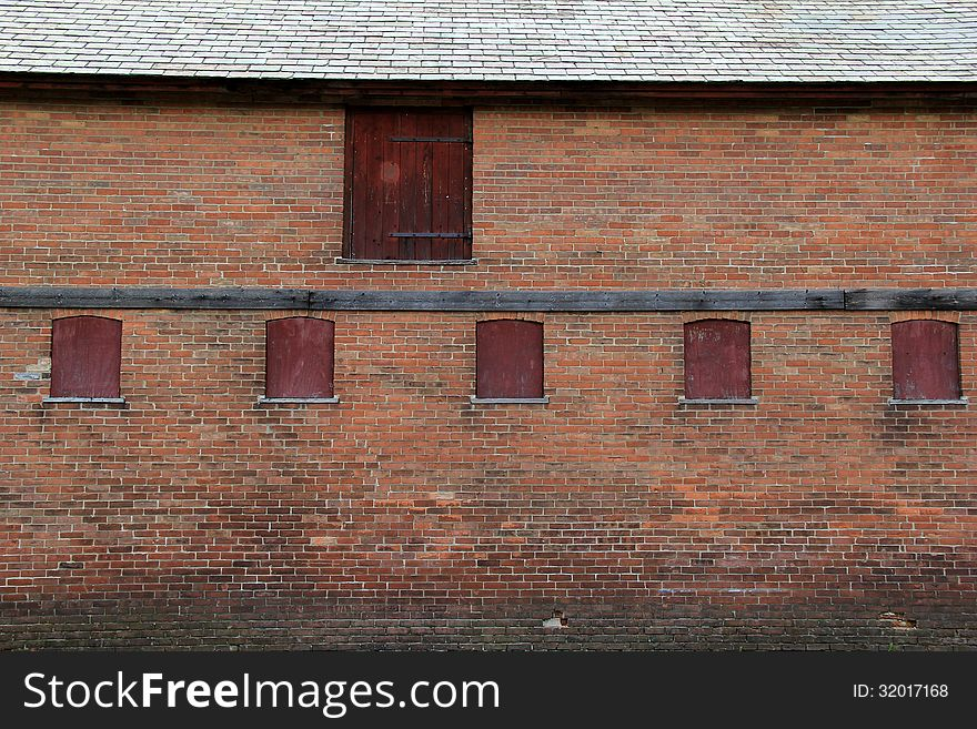 Old boarded up windows and doors in an old brick building