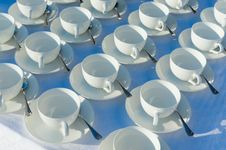 Free Stacked Empty Teacups With Teaspoons At A Function Over White Ba Royalty Free Stock Image - 32047776