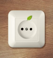 Outlet On Wooden Wall With Leaf. Go Green Power Concept. Stock Photo