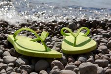 Green Flip-flops On The Pebble Beach Stock Photo