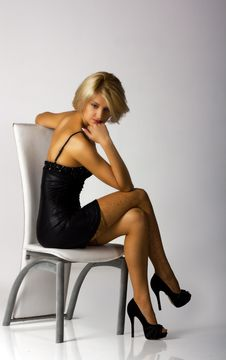 Young Beautiful Woman In Black Dress Sitting On A Chair Royalty Free Stock Images