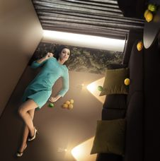 Extraordinary Beautiful Woman Lying And Relaxing On The Wall In The Overturned Room With Lemons Stock Image