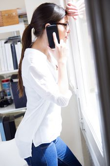 Woman Talking On Mobile Phone At Work Stock Photo