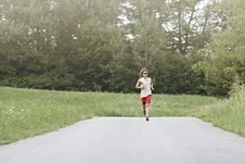 Free Athlete Runs In The Middle Of The Road Royalty Free Stock Photos - 32381978