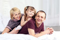 Free Little Girl, Father And Mother Lie On Bed And Smile Stock Photos - 32395703