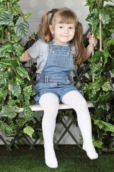 Free Happy Little Girl In Denim Jumpsuit Sits On Swing Royalty Free Stock Images - 32396129