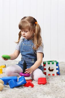 Free Happy Little Girl Gathers Pyramid Among Toys Stock Images - 32396164