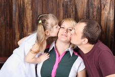Father And Little Daughter Kiss Mother Royalty Free Stock Photos
