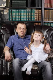 Man And Her Daughter Sit In Leather Armchair Stock Photos