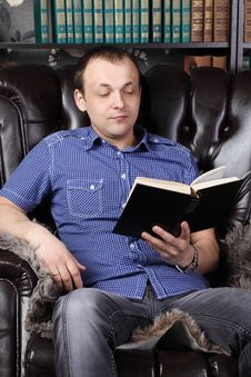 Young Man Sits In Leather Armchair And Reads Book Stock Photo