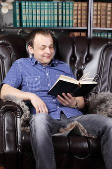 Smiling Man Sits In Leather Armchair And Reads Book Royalty Free Stock Images