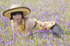 Free Brunette Lying Among Violet Flowers Stock Image - 32399601