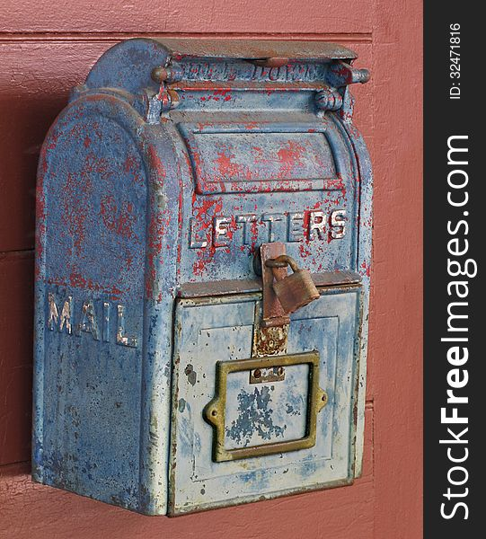 Old blue mailbox on a door.