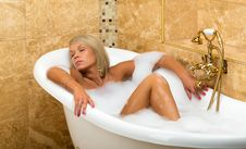 Tanned Girl Is Lying With His Eyes Closed In The Bathroom Royalty Free Stock Photography