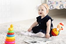 Free Little Cute Baby In Dress Sits On Soft Carpet Royalty Free Stock Image - 32795706