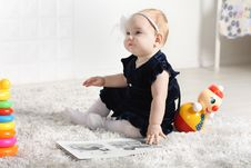 Little Cute Baby In Dress Sits On Carpet Stock Images