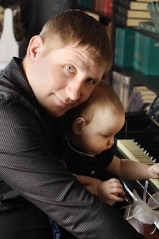 Cute Baby Sits At Knees Of Her Father And Touches Piano