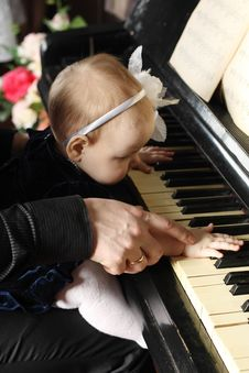 Free Cute Baby Sits At Knees Of Father And Plays Piano Royalty Free Stock Images - 32795739