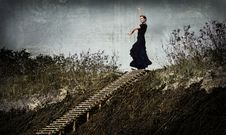 Free Enigmatic Woman In Black Dancing In The Dunes, On The Top Of The Stairs Royalty Free Stock Images - 32805189