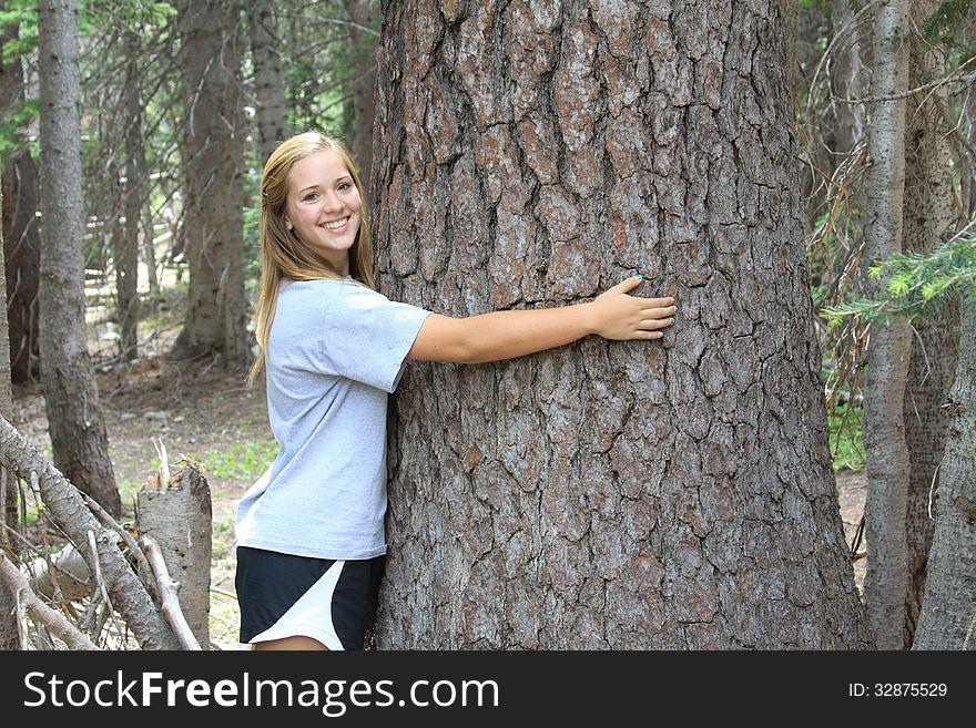 Athletic Teen Hugging Tree