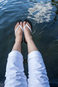 Free Feet Wearing Flip Flop Hanging Over A Lake Royalty Free Stock Images - 32885299