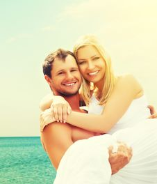 Happy Family Couple In Love Hugging And Laughing On The Beach Stock Photo