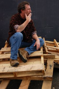 Smoking Man On Wood Pallets Royalty Free Stock Photo