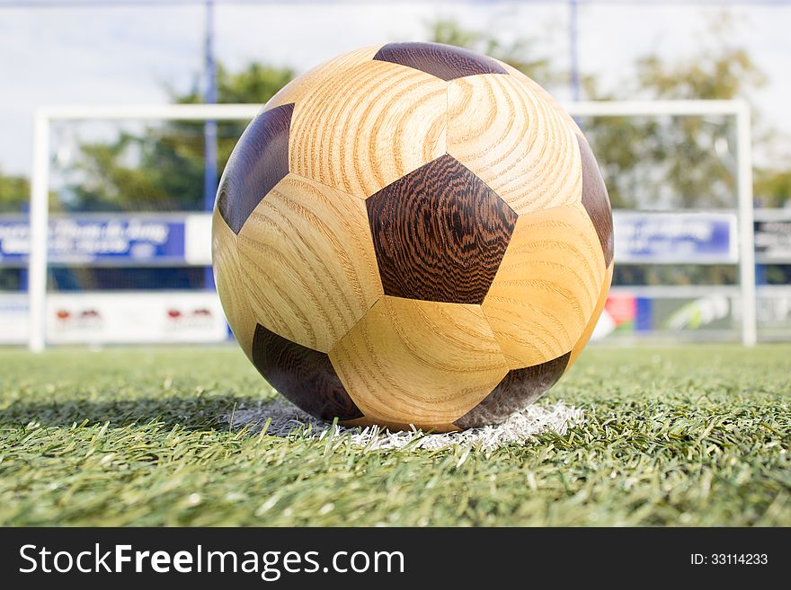 Wooden football on penalty spot with goal
