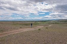 Free Man Goes Along Dirt Road Steppe Sky Royalty Free Stock Photography - 33157367