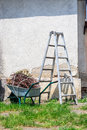 Free Metal Ladder And A Wheelbarrow By The Old Wall Stock Photography - 33291152