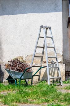 Metal Ladder And A Wheelbarrow By The Old Wall Stock Photography