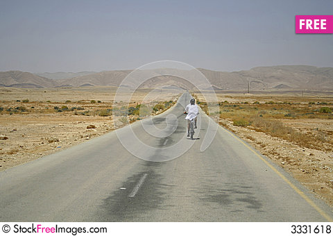 Free Man Cycling On Desert Road Royalty Free Stock Photos - 3331618