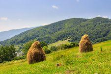 Haystacks On Hillside Near The Village Royalty Free Stock Image