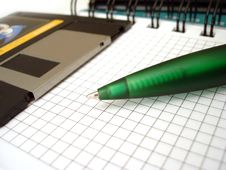 Pen And Diskette On Notebook Stock Image