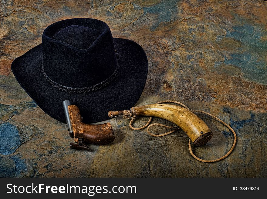 Antique pistol and powder horn with cowboy hat on slate