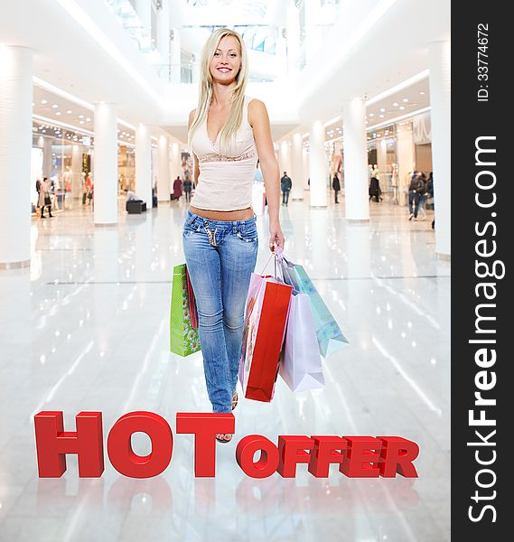 Woman with shopping bags poses at store