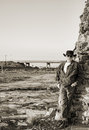 Free Cowboy Next To A Highway Leaning Against An Old Stone Chimney Royalty Free Stock Photo - 33919395