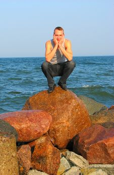 Free Young Man Sitting On A Stone Royalty Free Stock Image - 3400416