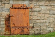 Rustic Metal Door In Stone Wall Stock Photo