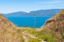 Free Grass Field With An Ocean And An Island In The Horizon. Royalty Free Stock Photography - 34074137