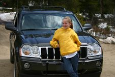 Teen Girl Standing In Front Of An SUV