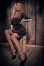 Free Blond Curly Hair Lady Sitting In A Pose On The Box Over Wooden Wall Background Royalty Free Stock Image - 34294996