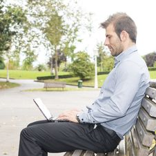 Free Man Sitting In The Wooden Bench And Working With Computer. Stock Photo - 34294320