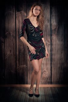 Beautiful Young Woman Standing In A Pose Over Wooden Wall Background Royalty Free Stock Photography