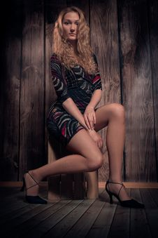Free Beautiful Blond Curly Hair Model Sitting In A Pose On The Box Over Wooden Wall Background Royalty Free Stock Image - 34294946