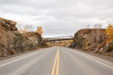 A Highway Between A Rock Ridge With A Bridge Overhead Royalty Free Stock Photo