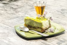 Slice Of Lime Cheesecake Decorated With Mint Flowers And Glass Of Cognac