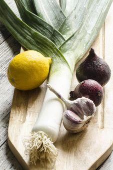 Fresh Onion, Garlic And Lemon On A Wooden Cutting Board. Royalty Free Stock Photos